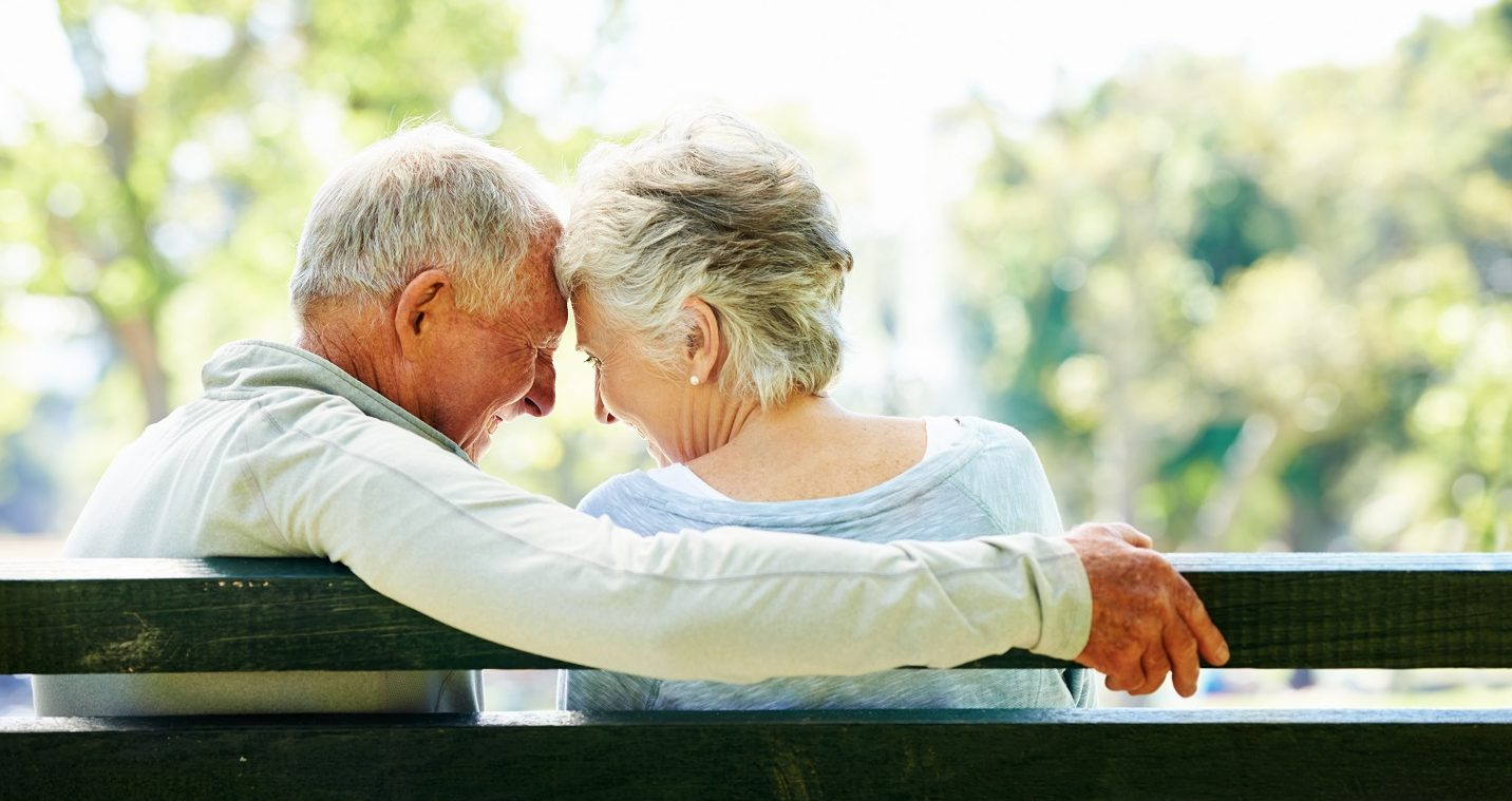 A happy senior couple relaxing together in their local park