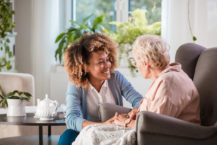 Friendly nurse helping an elderly woman