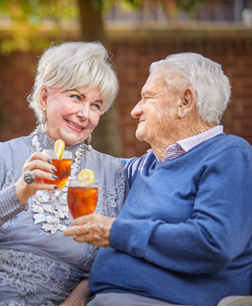 Couple holding ice teas and smiling at each other